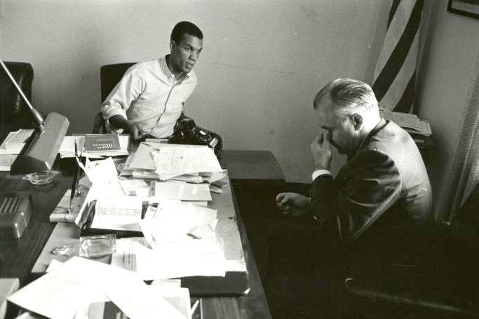 Young black man in a white button-down shirt speaking to an older white man in a suit while both are seated at a desk.